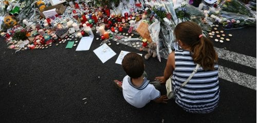 This photo taken on July 16, 2016 in front of Le Meridien hotel in Nice, southern France, shows children sitting next to flowers and candles placed in the road for victims of the deadly Bastille Day attack. The Islamic State group claimed responsibility for the truck attack that killed 84 people in Nice on France's national holiday, a news service affiliated with the jihadists said on July 16. Tunisian Mohamed Lahouaiej-Bouhlel, 31, smashed a 19-tonne truck into a packed crowd of people in the Riviera city celebrating Bastille Day -- France's national day. / AFP PHOTO / ANNE-CHRISTINE POUJOULAT